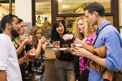 Group standing while enjoying tapas and drinks in Sevilla