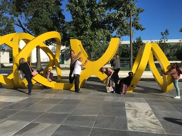 Group poses on a large yellow sculpture in a building square