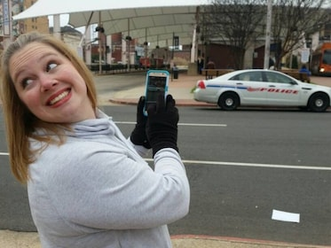 Woman smiles and holds up her phone next to a street