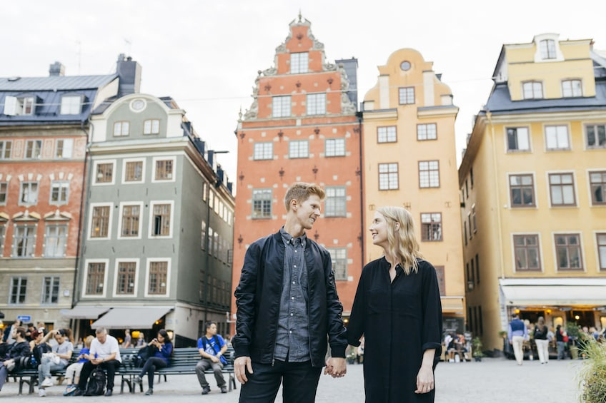 Show item 1 of 4. Couple holding hands while standing in Gamla stan