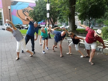 Tour group pulling shapes with their bodies on the street
