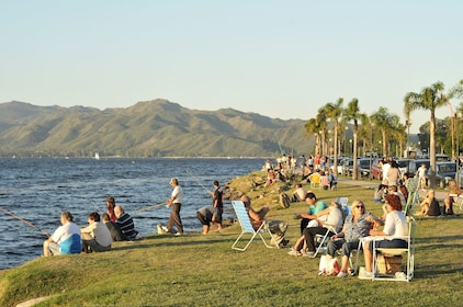 Gathering of people sit next to the water in Villa Carlos Paz