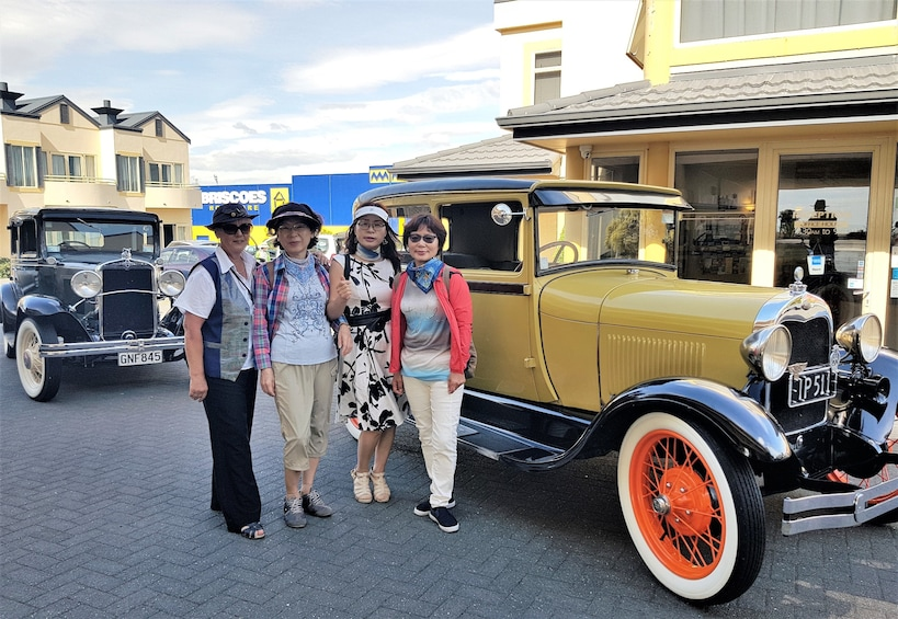 Show item 6 of 6. Guests taking photos next to stunning authentic classic and vintage cars at the Art Deco City of Napier