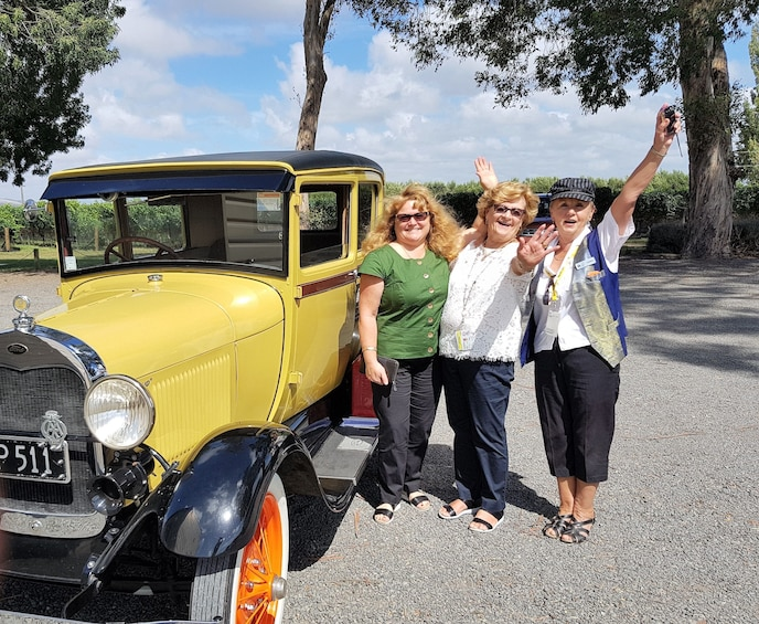 Show item 1 of 6. Group of woman taking photos next to a  taking photos next to stunning authentic classic car at the Art Deco City of Napier