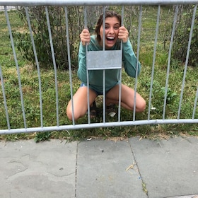 Woman holding onto a fence on a zombie scavenger hunt in Cincinnati