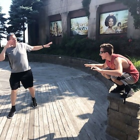 A man standing with his arms out and another man squats with his arms raised