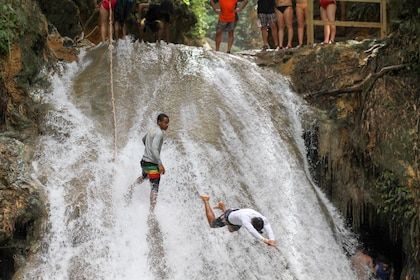 Men playing on a waterfall rock in Jamaica
