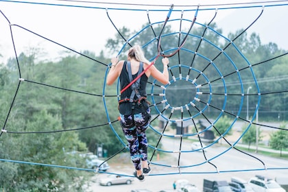 Woman climbing on a rope web at an aerial adventure park in British Columbia