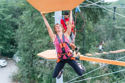 Woman harnessed to a rope hanging from a platform in the air at an aerial adventure park in British Columbia