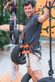 Man in a harness walking on tires at aerial adventure park in British Columbia