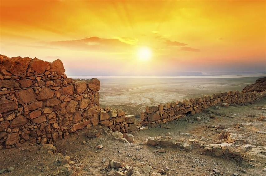 Show item 2 of 10. Remains of a stone wall in Masada at sunset