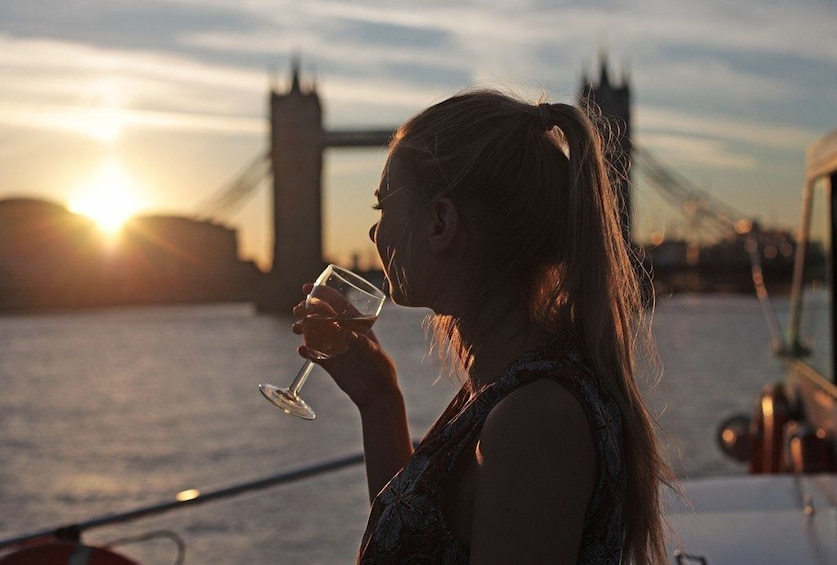 Show item 1 of 7. Silhouetted woman drinking wine on a evening cruise on the river Thames