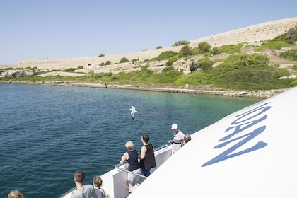 Guests taking in the beautiful views from a glass bottom boat in Mahón