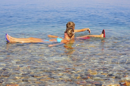 Mother and child floating in the salty water of the Dead Sea