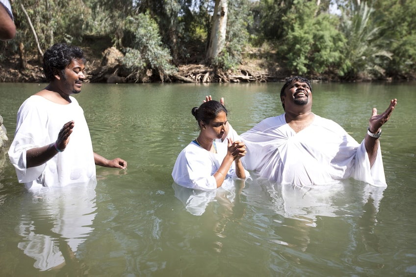 Show item 5 of 5. People getting baptized in the waters of the Jordan River