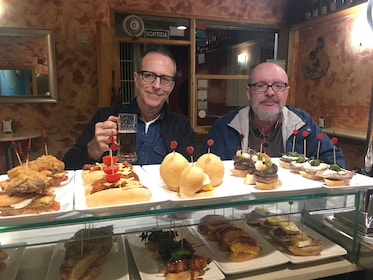 Two men enjoying drinks and food on the tapas evening walking tour in Barcelona