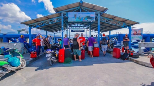 Tourists with baggage wait at Thongsala Pier in Thailand