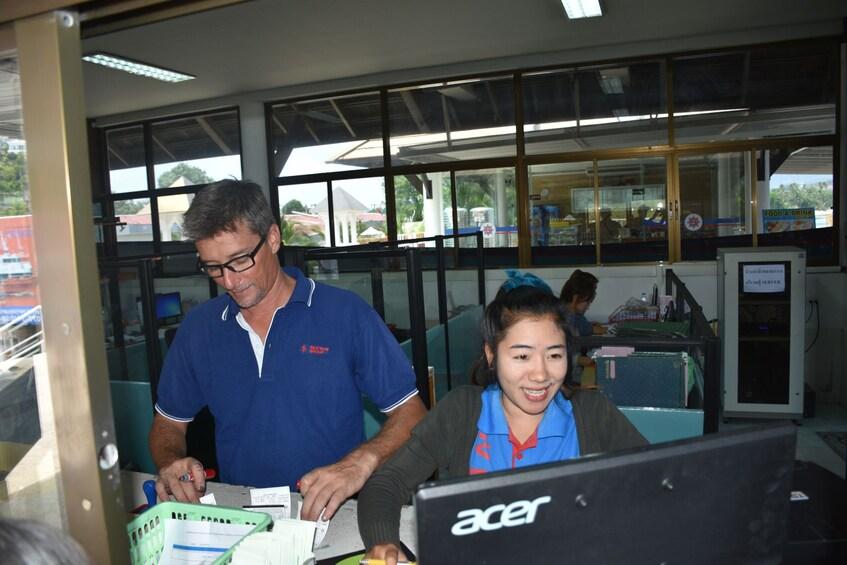Show item 5 of 7. Seatran employee helps customer