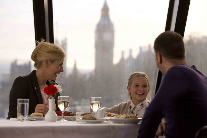 Show item 3 of 7. Family having lunch on a River Thames cruise with Big Ben in the background
