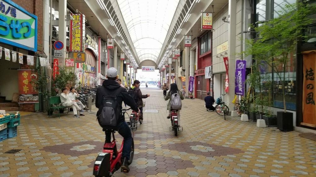 Group riding electric bikes through a street in Hiroshima
