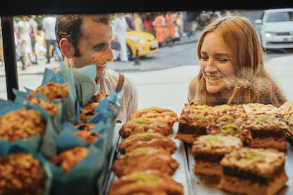 Two people looking at Baklava in a bakery window