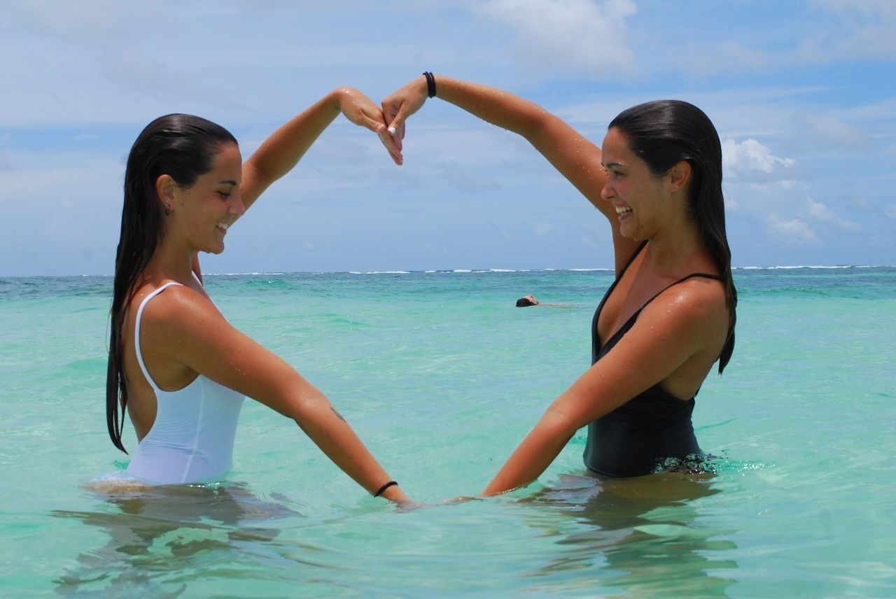 Two ladies making a heart shape with their arms at a beach in Punta Cana