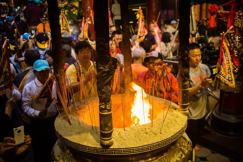 Show item 3 of 3. Visitors burning incense at a temple in Taiwan