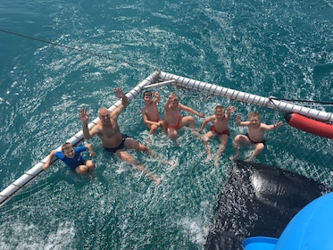 Family playing in a swim net attached to dolphin discovery cruise boat in New South Wales