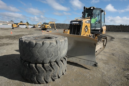 Bulldozer closing in on two large tires