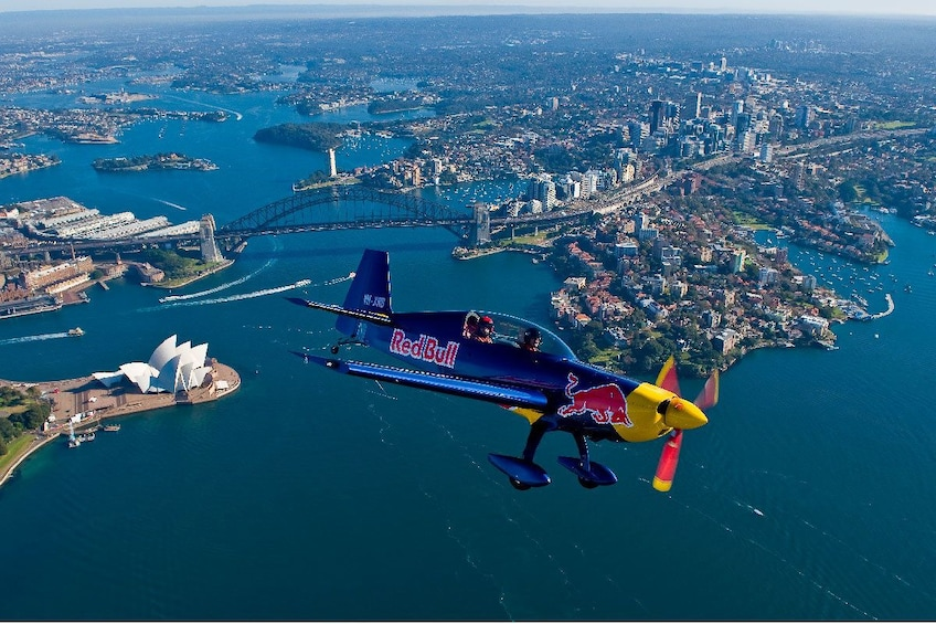 Show item 1 of 4. Small airplane flying over the city in Sydney