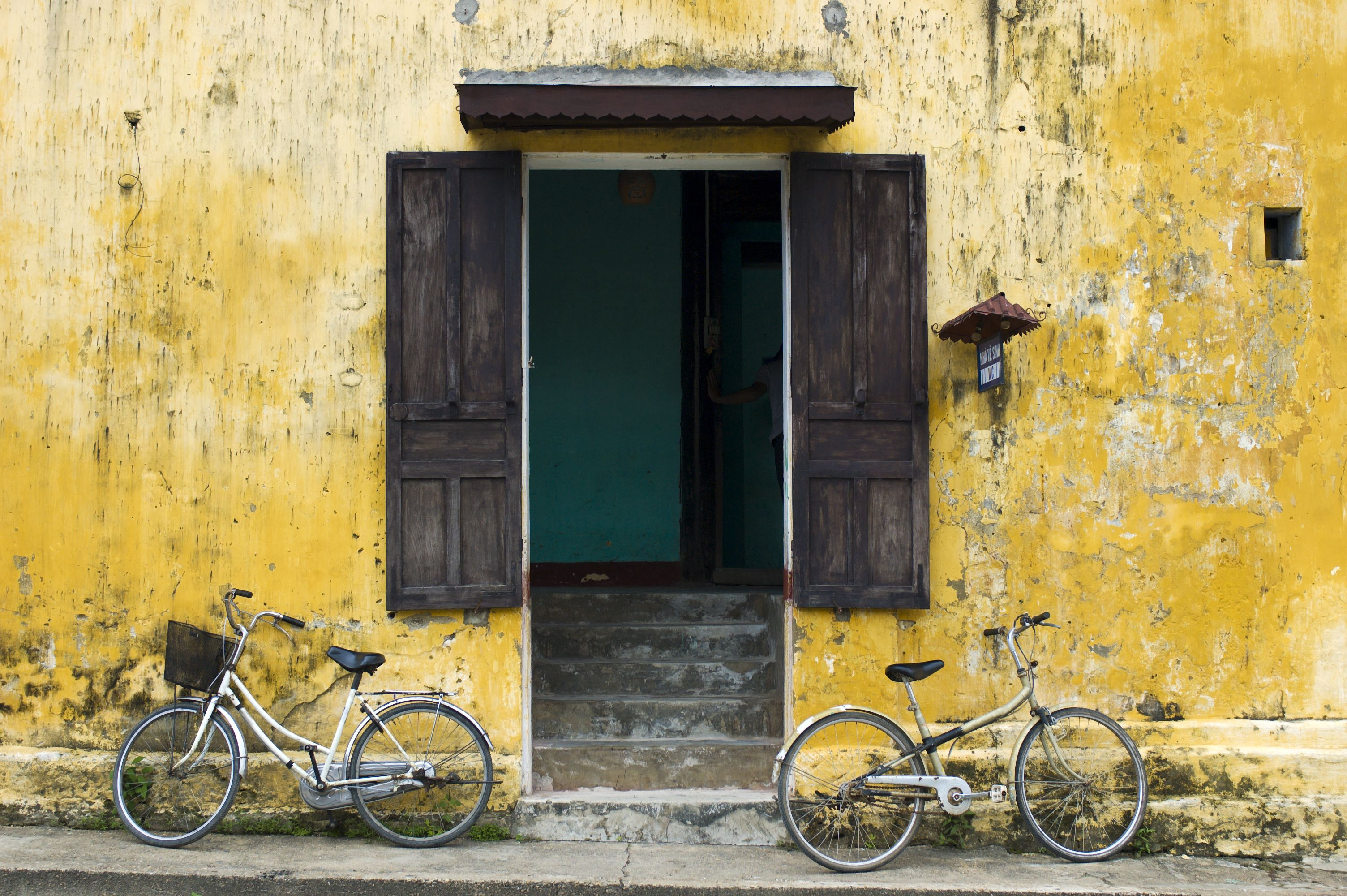 Bicycles parked outside a yellow building in Hoi An