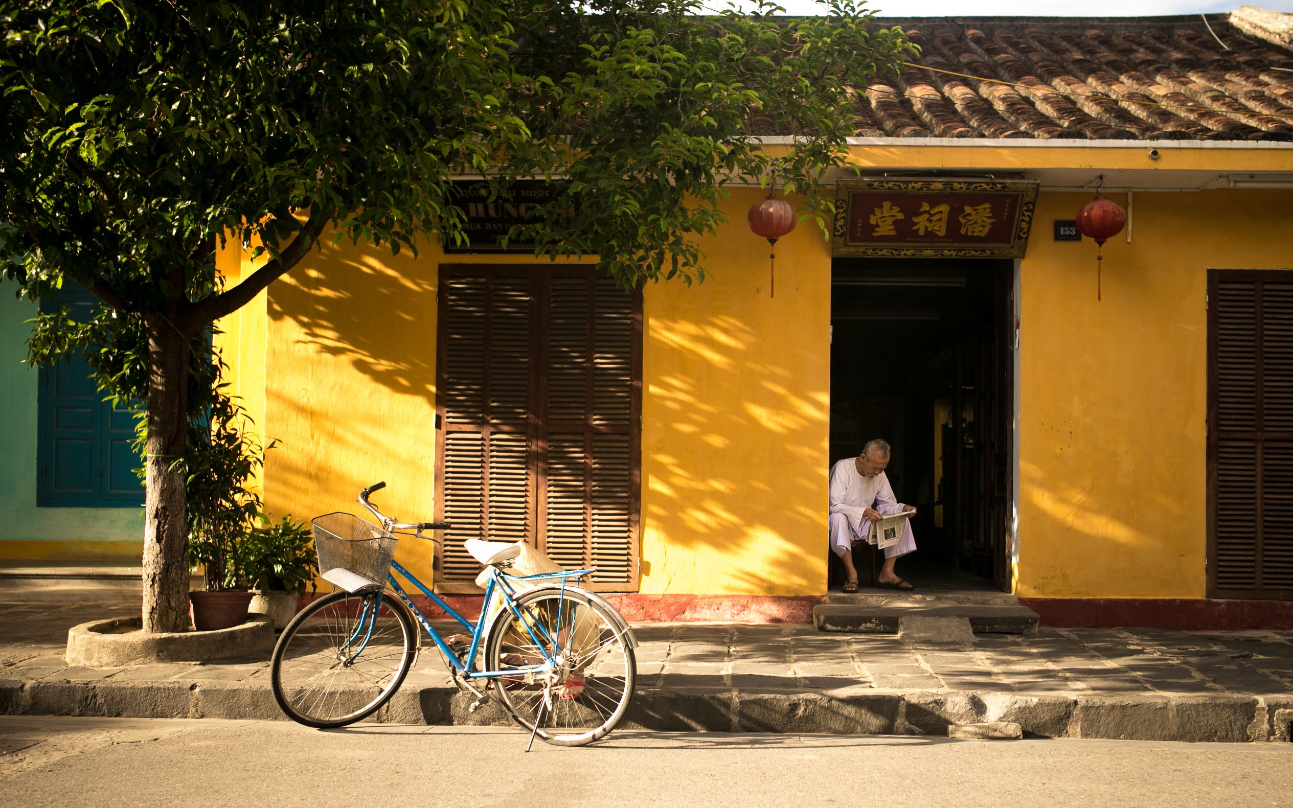 Bicycle parked outside a yellow building in Hoi An
