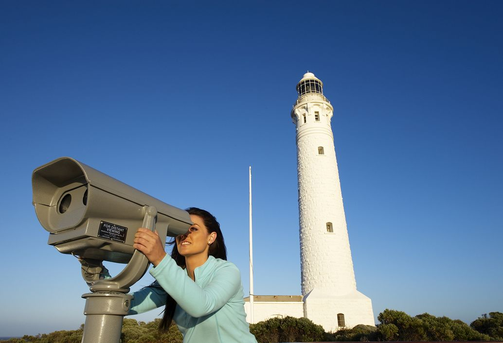 Person looking through a telescope next to a Lighthouse