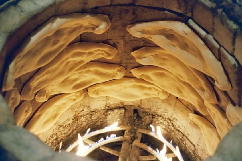 Show item 2 of 4. Traditional Georgian bread in an oven