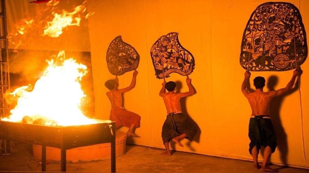 Show item 5 of 10. Three men hold up large fans against wall with fire behind them
