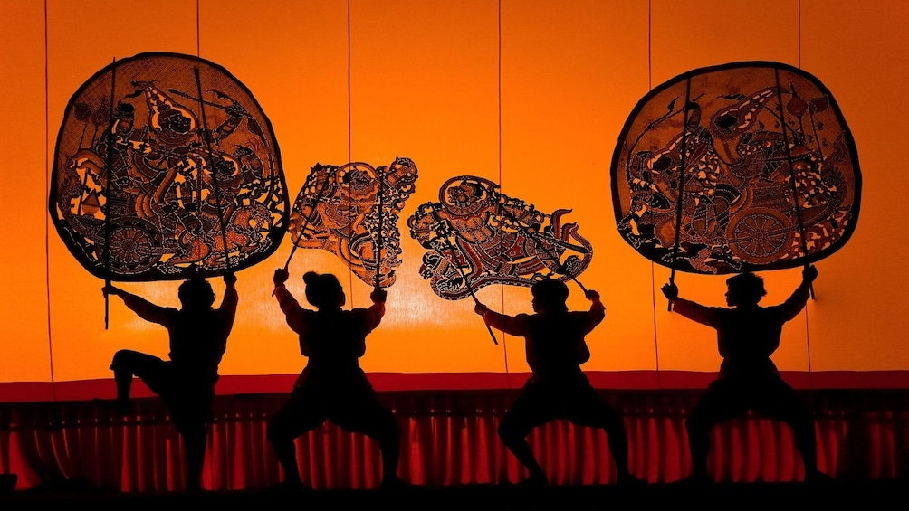 Show item 1 of 10. Silhouettes of performers holding under intricate fans in front of orange backdrop