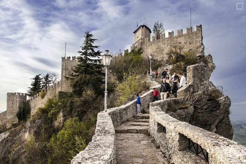 People walking up stone stairs to the top of mountain in San Marino