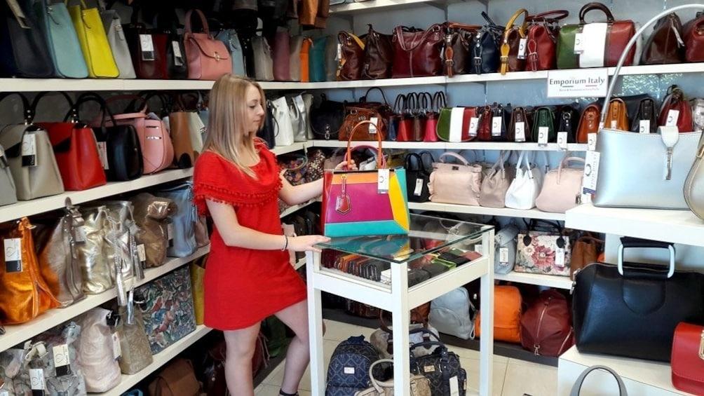 Woman shopping for handbags at a shop in San Marino