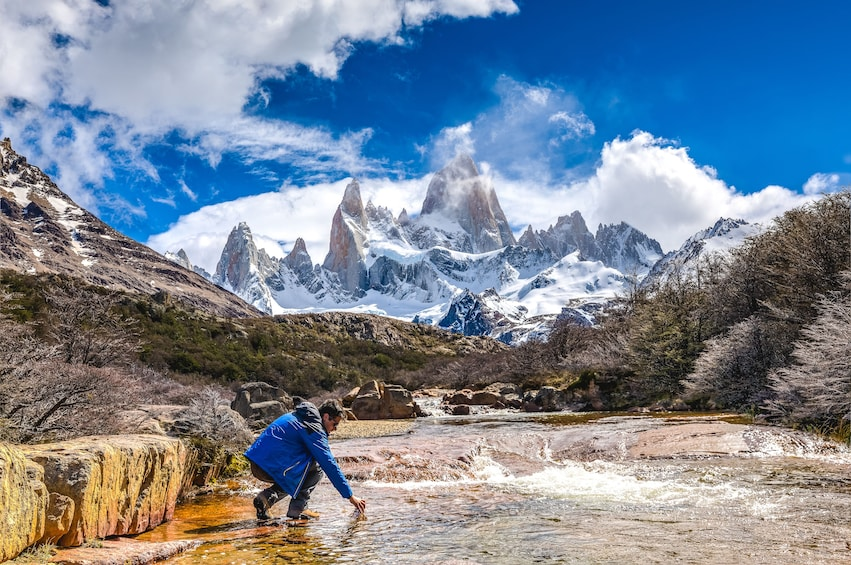 Show item 2 of 8. Man kneels in water with trees and mountains of Patagonia in the background