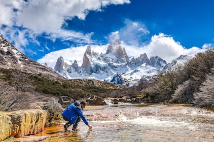 Man kneels in water with trees and mountains of Patagonia in the background