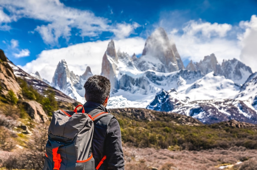 Show item 1 of 8. Man stands looking at the mountains of Patagonia