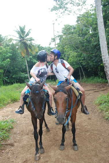 A couple on horses kiss during a trail ride