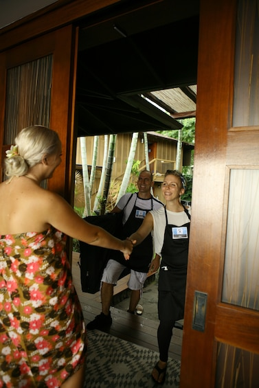 Show item 2 of 7. Woman greeting massage therapists at her door on Hawaii Island