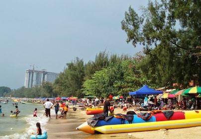Sunny day view of the banana boats, and visitors swimming at Port Dickson