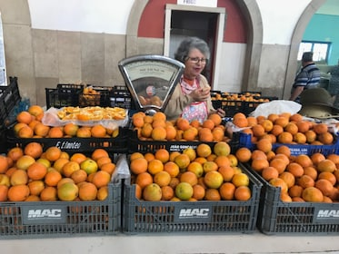 Fruit vendor surrounded by oranges in Portugal