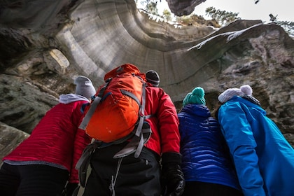 Winter hikers look up at a rock formation