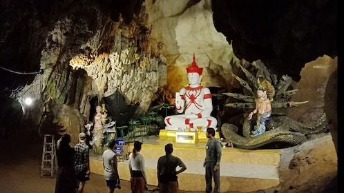 Tour group with guide looking an underground religious shrine in Chiang Mai