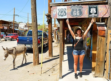 Woman under historic Route 66 sign in Oatman