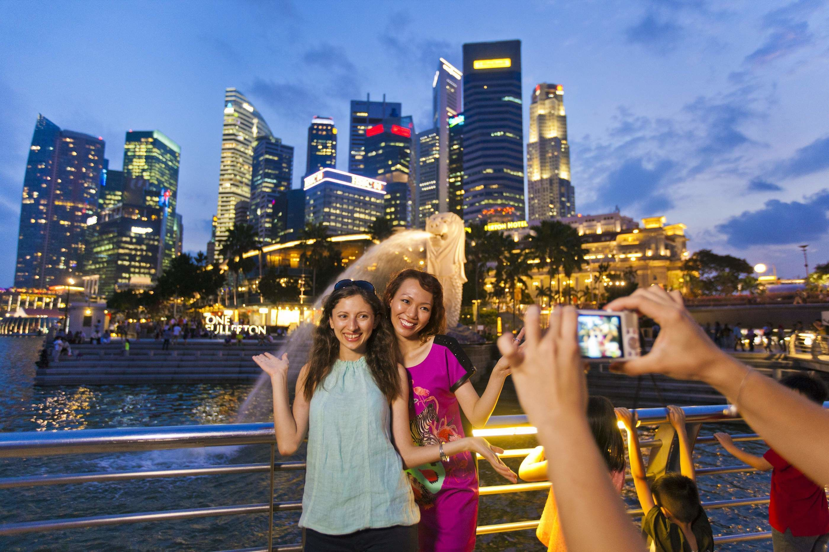 Women posing for a photo at night with the city in the background in Singapore