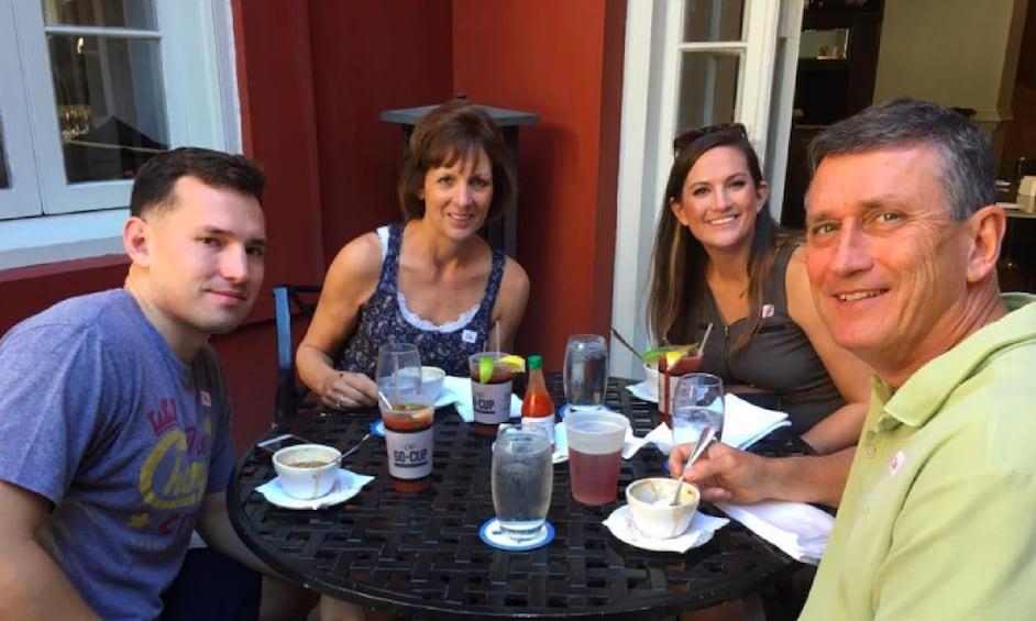 Show item 1 of 2. Family with food and drinks at a table outside in New Orleans